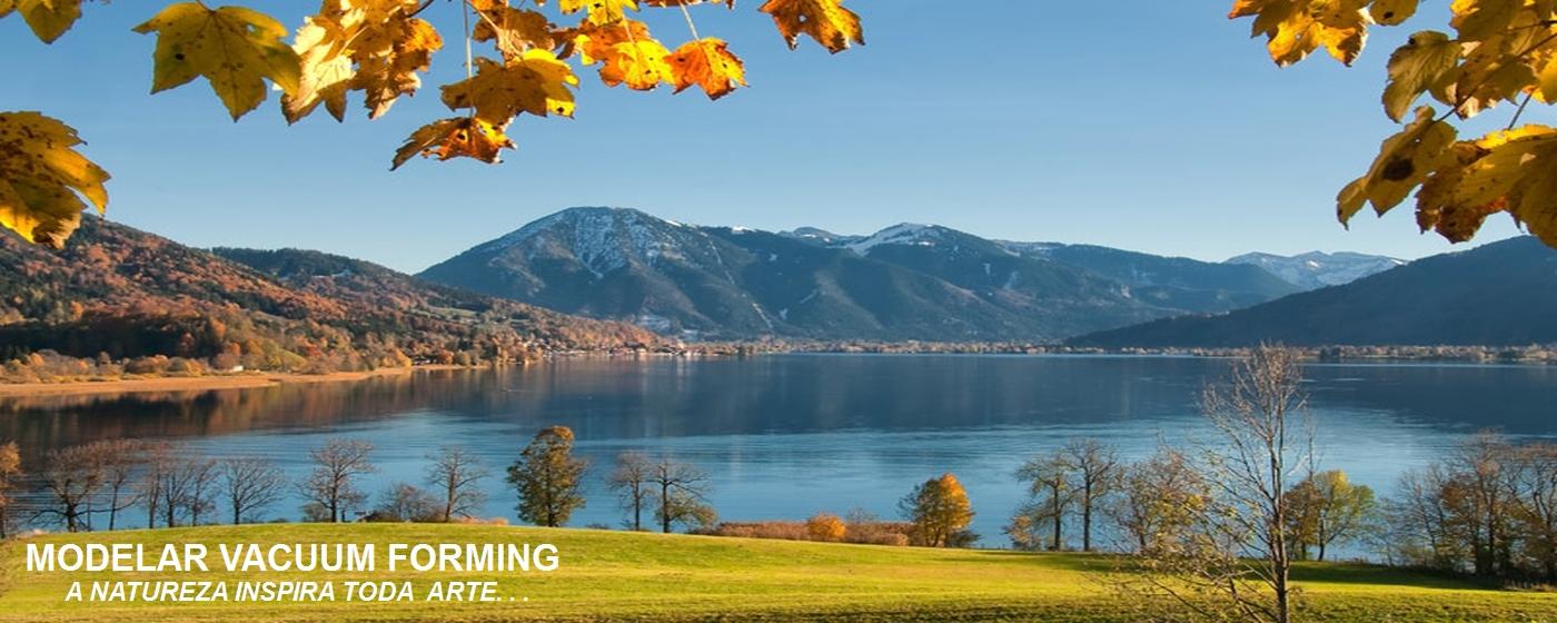 Imagem de capa da pagina Apresentação, cena da natureza onde figura as águas do lago e ao fundo as montanhas, em primeiro plano na parte de cima da cena folhas de uma arvore em cor douradas iluminadas pelo sol se destacam.